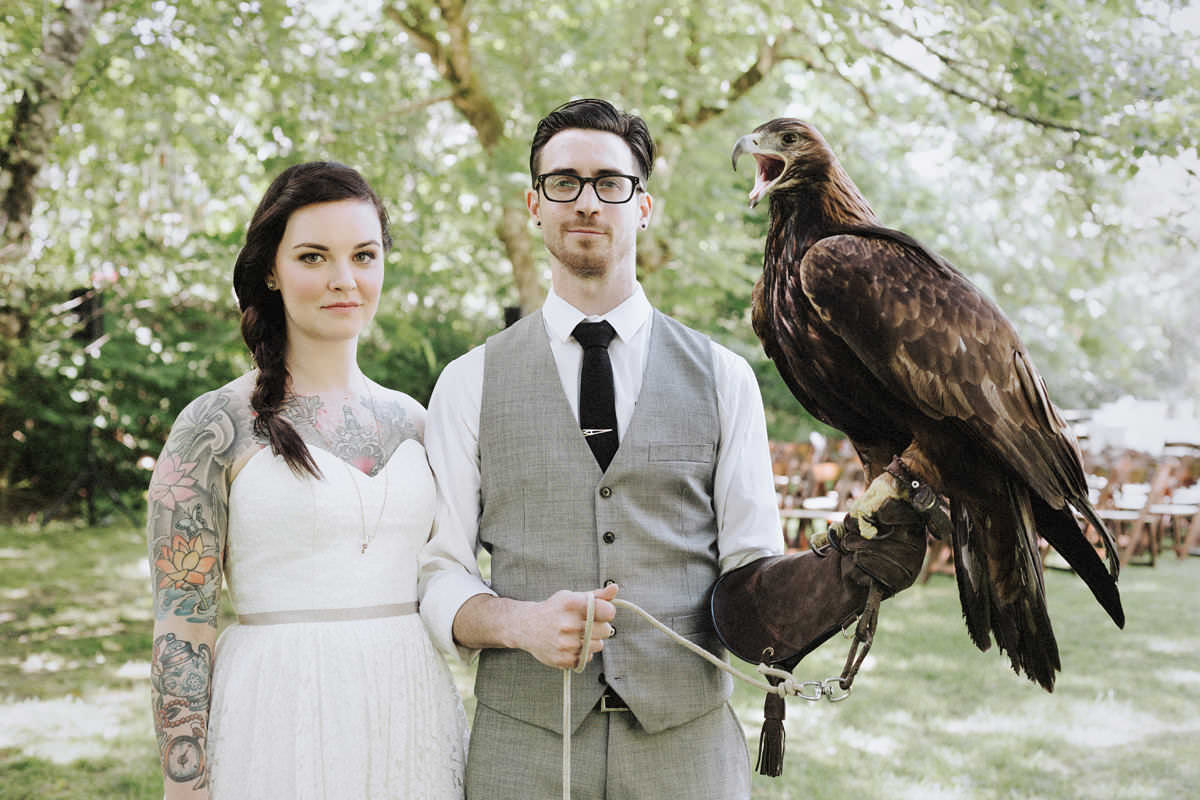 tattooed couple holding hawk