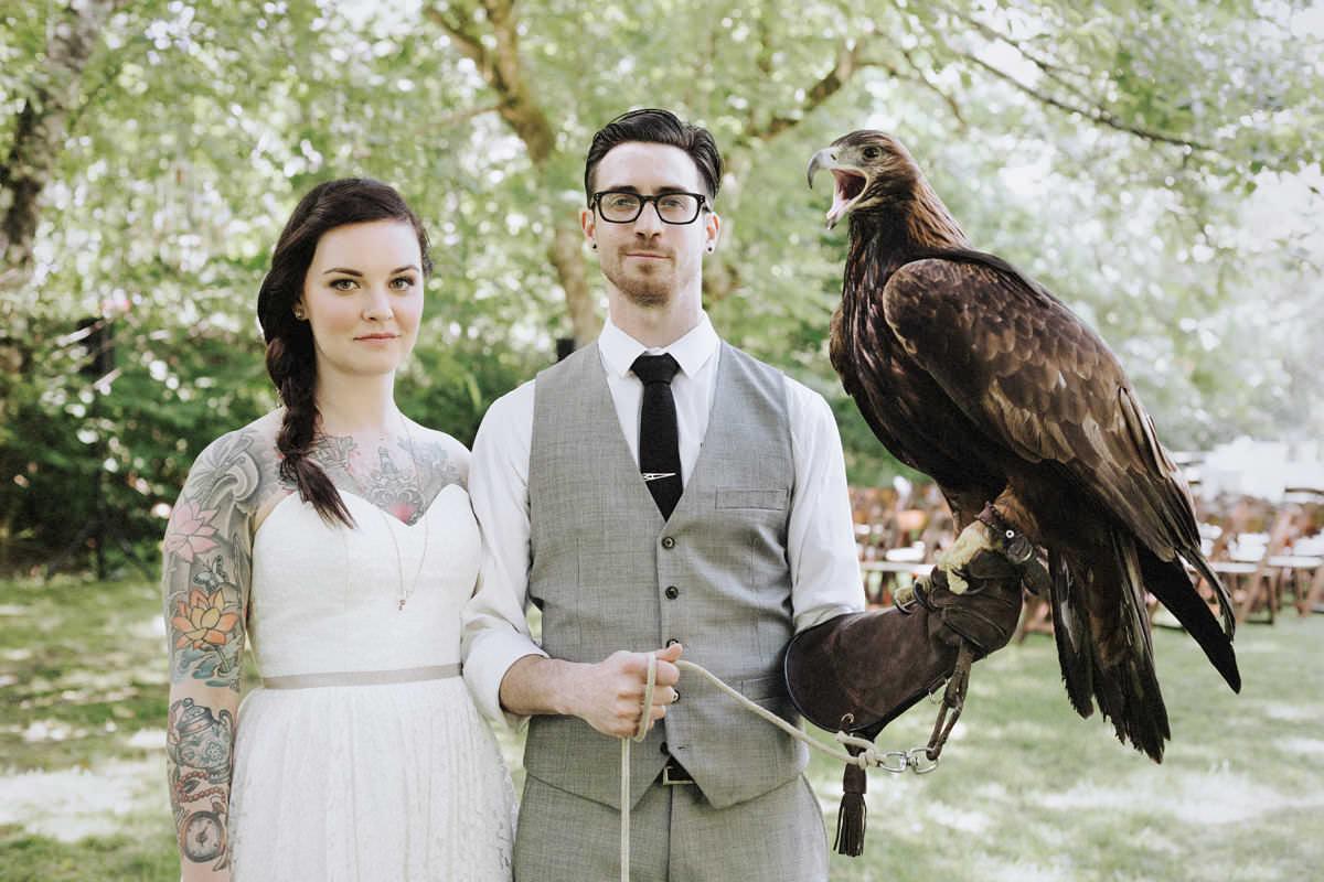 tattooed couple holding hawk