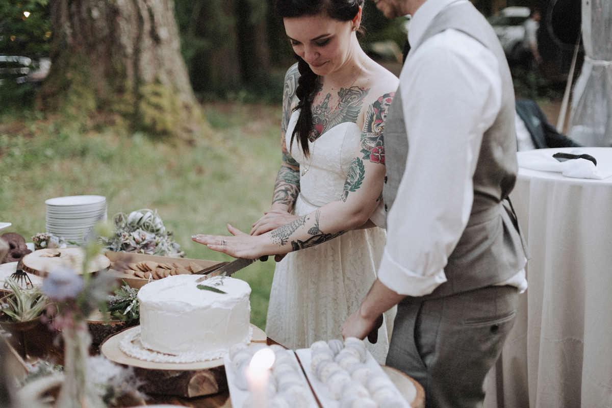 tattooed bride cutting cake whistler