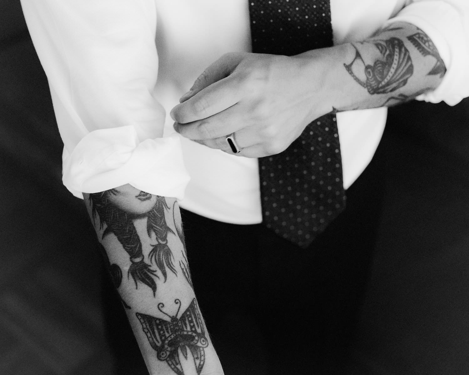 tattooed groom rolling up sleeve during morning prep