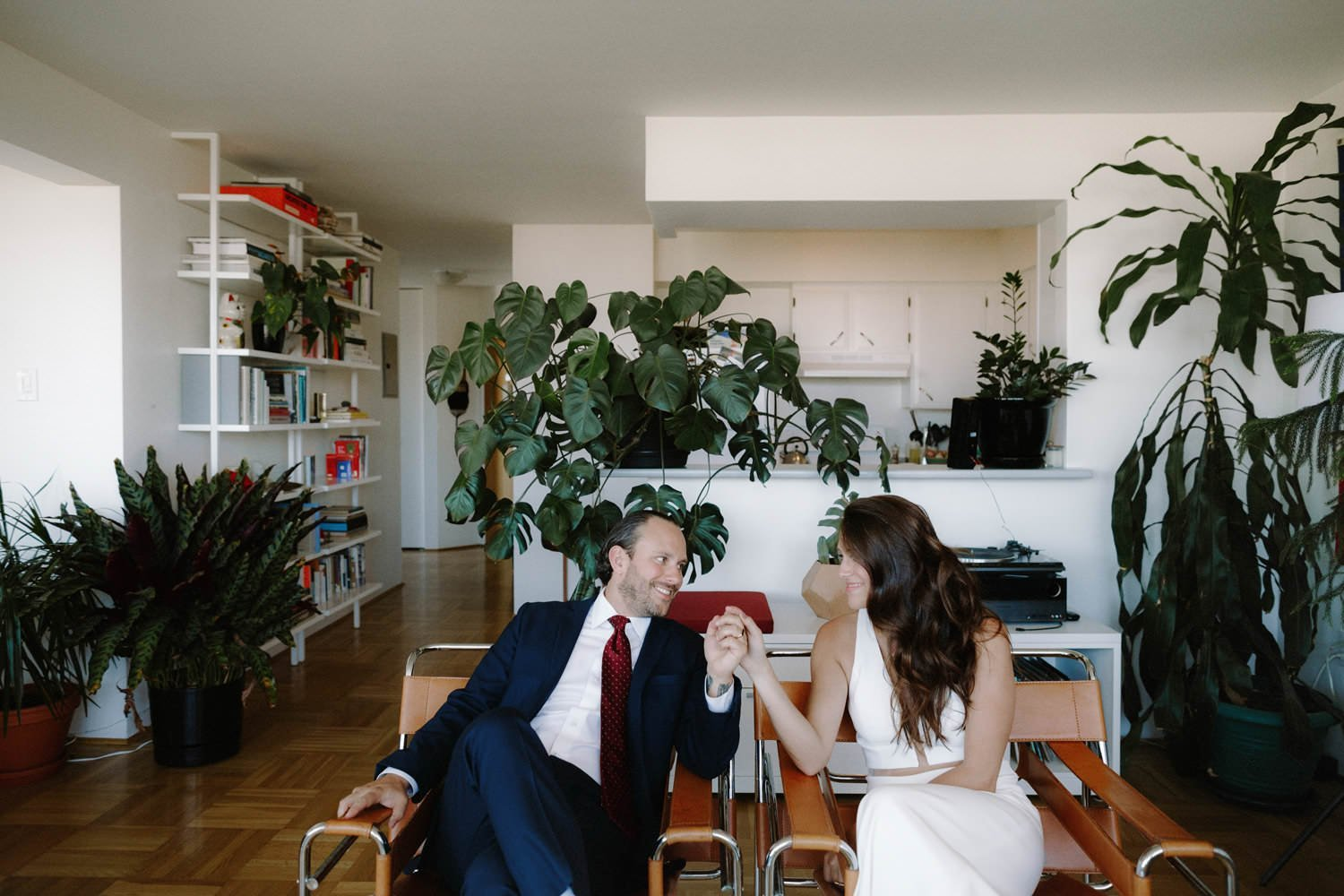 bride and groom with matching marcel breuer wassily chairs in their mid century modern vancouver apartment