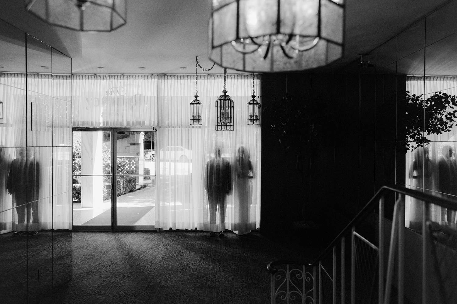 bride and groom behind curtain in their apartment lobby