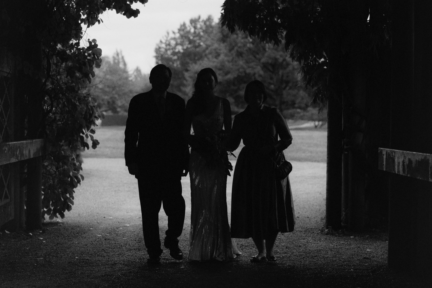 bride walking through arbour with father and mother at ubc botanical garden
