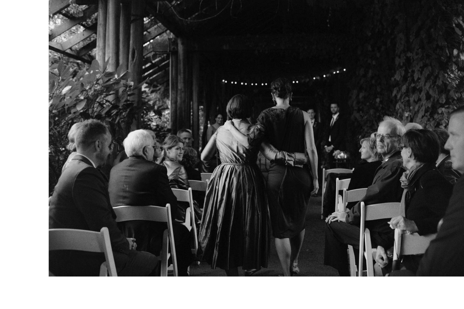 two women walking down aisle under arbour at ubc botanical garden wedding