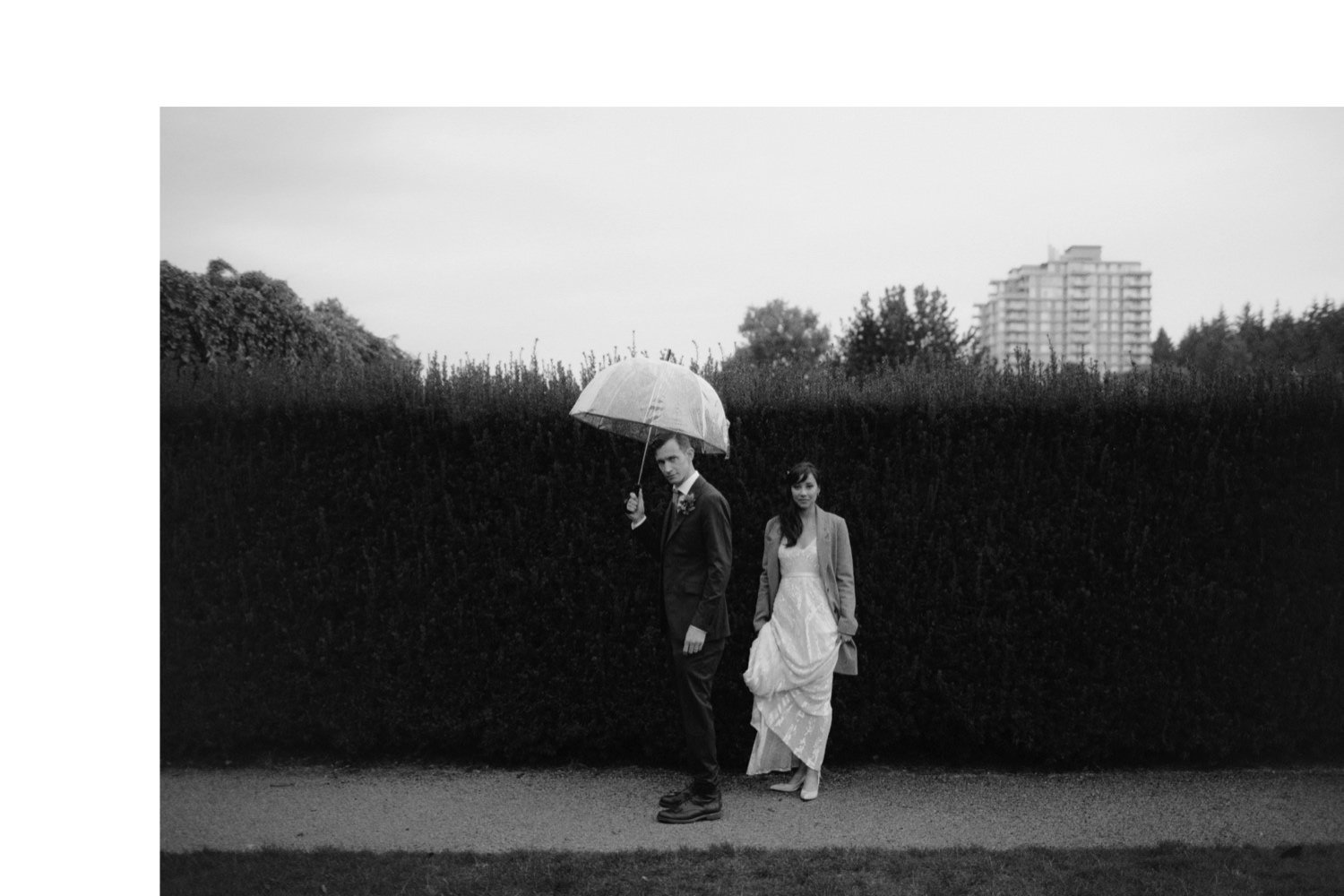 groom holding clear umbrella while bride wears wool coat