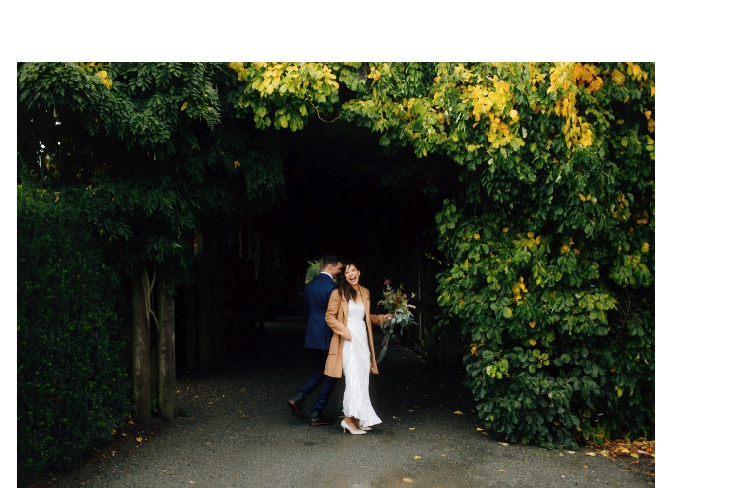 bride and groom standing outside arbour at ubc botanical garden
