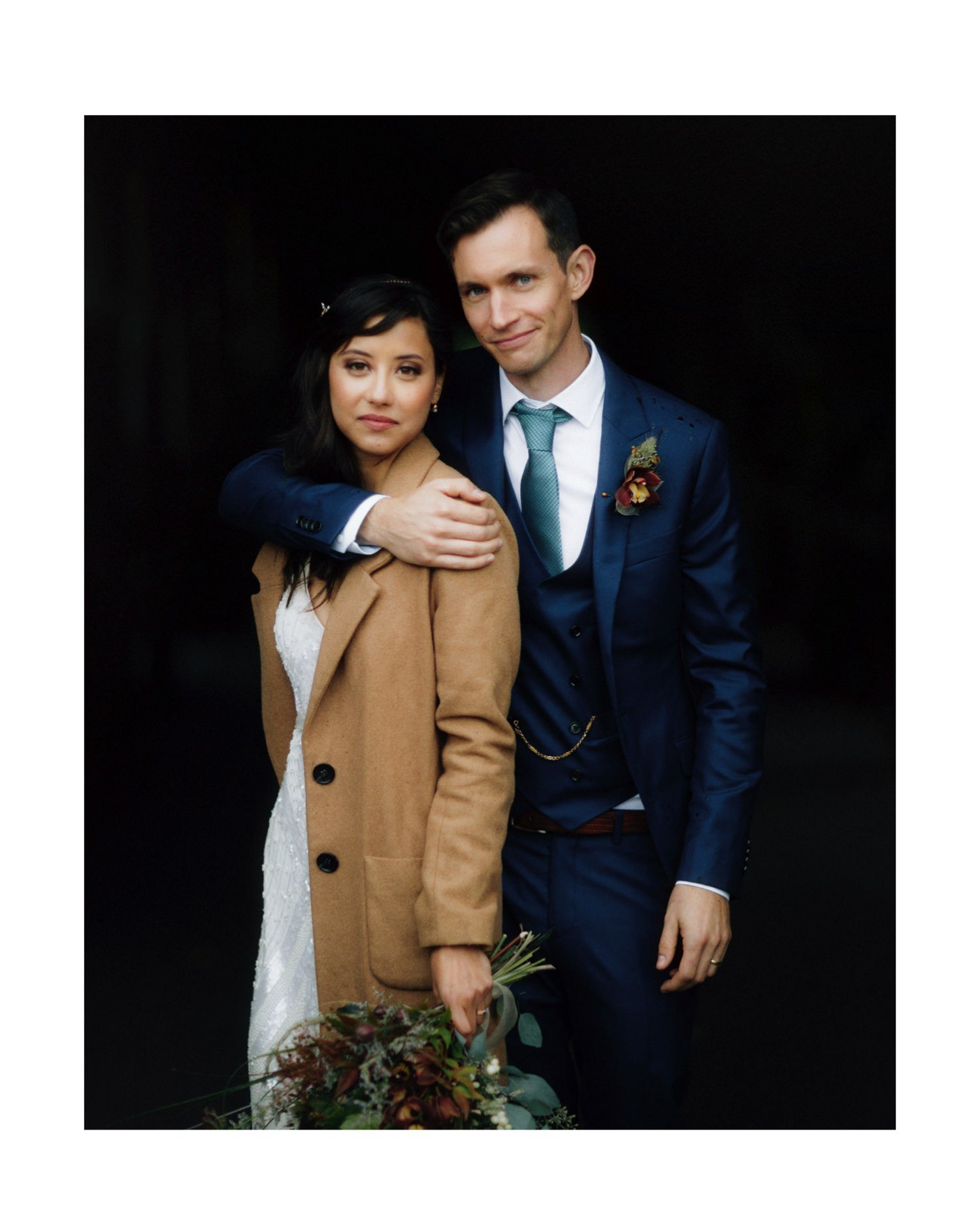 bride wearing beige wool coat and groom wearing tailored navy suit and watch chain