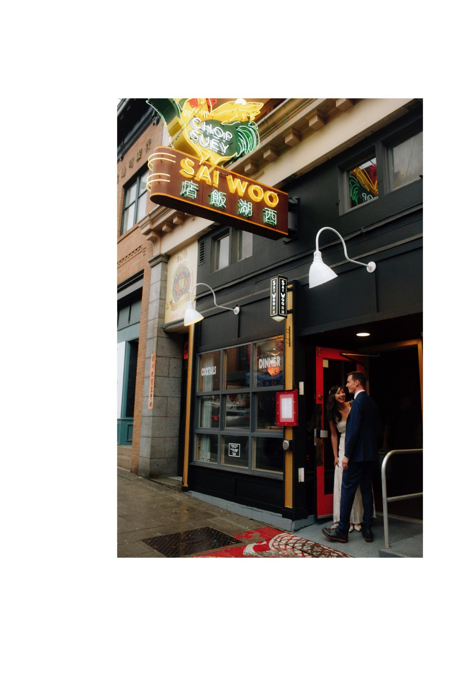 bride and groom under original neon rooster sign at sai woo vancouver